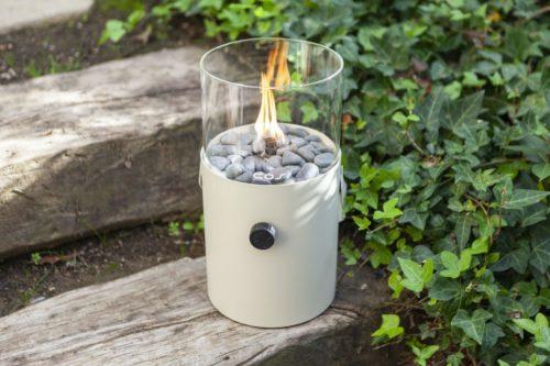 Fuego de sobremesa a gas Cosiscoop Original Marfil que proporciona una atmósfera cálida y acogedora. Manejable y fácil de utilizar. Ideal para el jardín. Con asa incorporada, es portátil. Tiene un diámetro de 16 cm y una altura total con cristal incluido, de 30 cm. Se alimenta de un cartucho a gas de 190 gramos. Con solo girar el botón de encendido y acercar un encendedor largo, se consigue mantener la llama durante más de 6 horas. Incluye pequeñas piedras que se colocan alrededor del quemador.