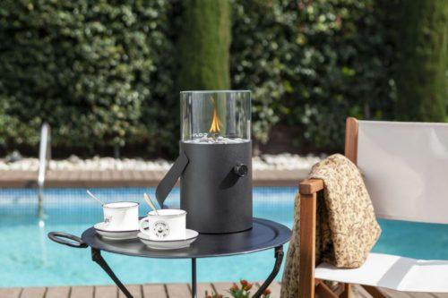 Fuego de sobremesa a gas que proporciona una atmósfera cálida y acogedora. Manejable y fácil de utilizar. Ideal para el jardín. Con asa incorporada, es portátil. Tiene un diámetro de 16 cm y una altura total con cristal incluido, de 30 cm. Se alimenta de un cartucho a gas de 190 gramos. Con solo girar el botón de encendido y acercar un encendedor largo, se consigue mantener la llama durante más de 6 horas. Incluye pequeñas piedras que se colocan alrededor del quemador.