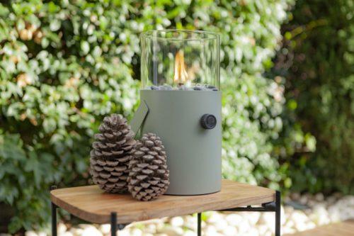 Fuego de sobremesa a gas Cosisscoop Original Verde Oliva que proporciona una atmósfera cálida y acogedora. Manejable y fácil de utilizar. Ideal para el jardín. Con asa incorporada, es portátil. Tiene un diámetro de 16 cm y una altura total con cristal incluido, de 30 cm. Se alimenta de un cartucho a gas de 190 gramos. Con solo girar el botón de encendido y acercar un encendedor largo, se consigue mantener la llama durante más de 6 horas. Incluye pequeñas piedras que se colocan alrededor del quemador.